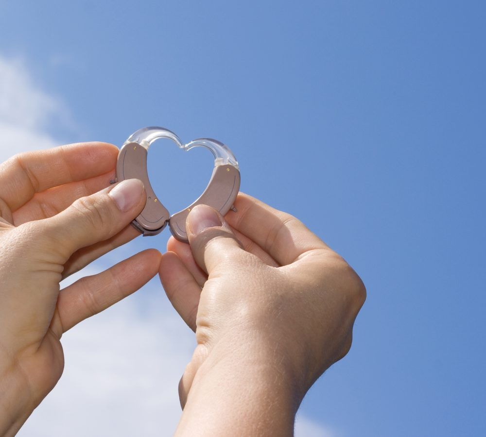 Hands showing a heart shape from digital hearing aids in fron of a blue sky background